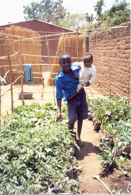 2009 - Chrispin and his little brother showing tomatoes and other vegetables growing in containers with a minimum of irrigation water.  With container gardening a lot of water is saved for other purposes (no infiltration in the dry soil, less evaporation from the plastic bags).