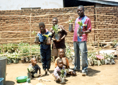2009 - Patrick Harry with some members of the FOM Kids Club showing spinach plants growing splendidly in plastic bags.  Drought has no effect on plant growth, because the substrate in the bags is kept humid with only a bit of irrigation from time to time.