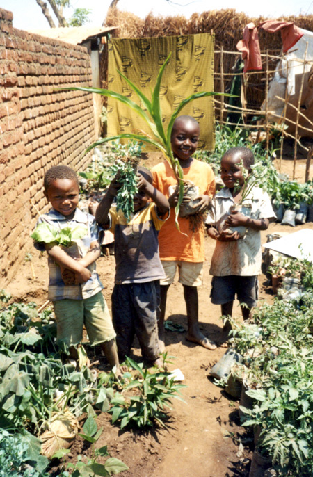 2009 - Tibo, Patrick Harry's son, with some of his friends, proudly showing different vegetables grown at the container gardening project site.