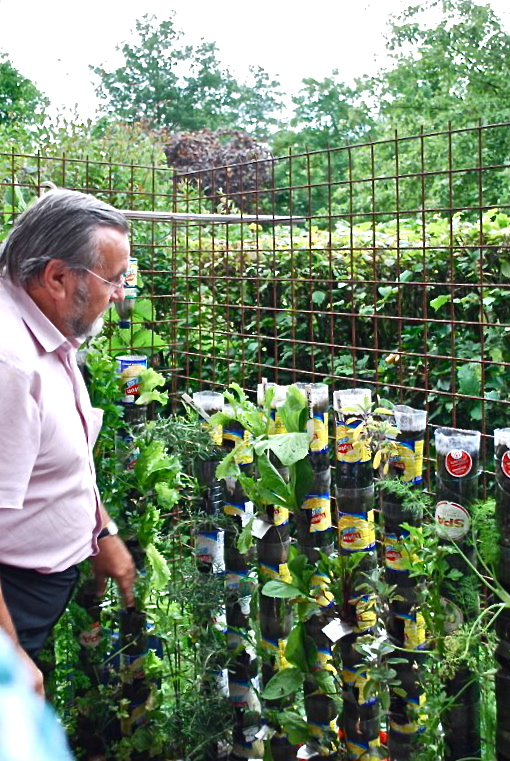 Prof. Dr. Willem Van Cotthem checking the first results of his bottle tower experiments : vegetables and herbs growing in recycled bottles. (Photo WVC).