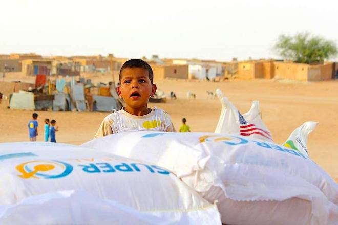 A small child peeks from behind the sacks of dry food distributed in the Laayoune camp, South West Algeria. - Photo: Dominik Sipinski - Article here: http://www.joinmagazine.co.uk/article/a-permanent-crisis-in-the-desert/ - https://scontent-fra3-1.xx.fbcdn.net/hphotos-xft1/v/t1.0-9/11109666_10153449833530844_2918553993613655361_n.jpg?oh=95c08463cb5220695bf56ea0849cf96e&oe=5696E2C0