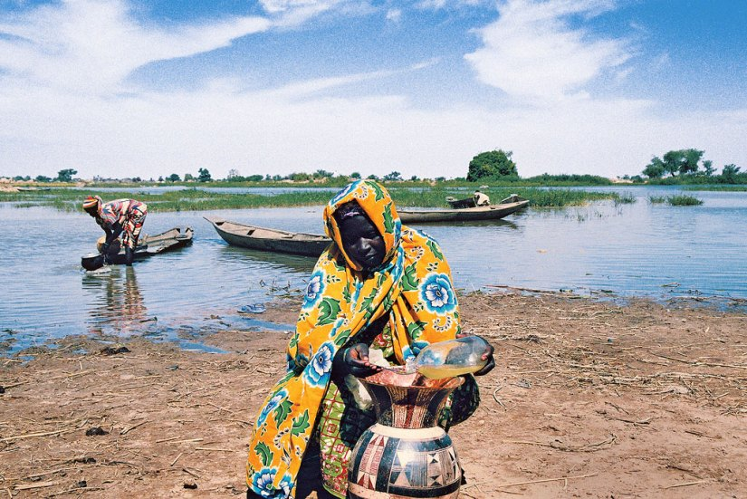 In the Liptako-Gourma region, Niger, an area that has experienced large-scale land degradation and water scarcity, a villager takes extra precautions to keep her supply of water clean. Photo: UNDP/Rabo Yahaya